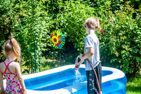 Little boy and girl filling swimming pool with water Imagens