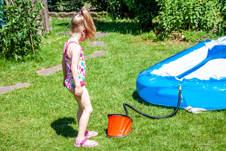 Little girl blowing up inflatable swimming pool