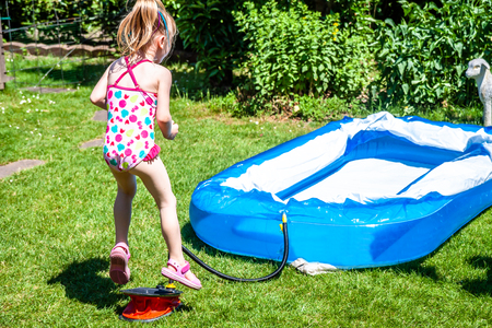 Little girl jumping on the bellows to blow up swimming pool