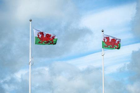 Flag of Wales on the mast with clouds in the background