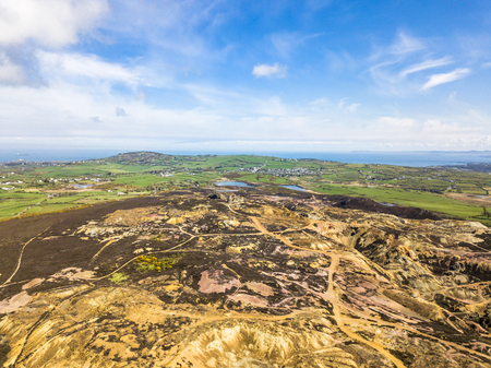 The colourful remains of the former copper mine Parys Mountain near Amlwch on the Isle of Anglesey, Wales, UK.