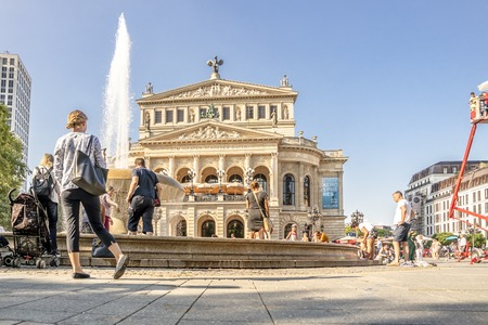 Frankfurt / Germany - August 02 2018: People searching for refreshment in the water of the fountain at Opernplatz during one of the warmest summer days in the city