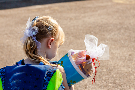 Little girl standing in front of the school building holding her candy cone.