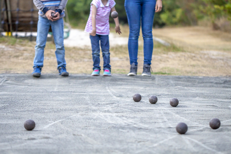 Family playing with balls on gravel at leisure