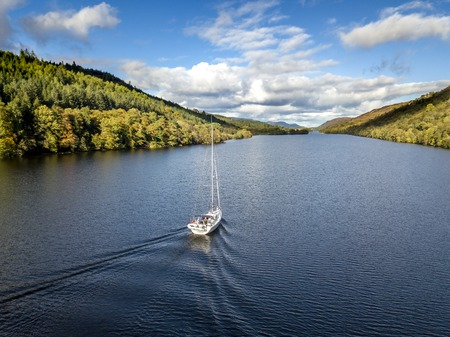 Flying through the Great Glen above Loch Oich towards Loch Ness behind a white motor yacht in the scottish highlands - United Kingdom