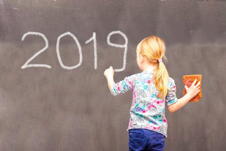 Cute little girl writing 2019 on chalkboard in school