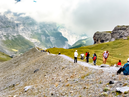 Interlaken / Switzerland - September 09 2008 : Marathon runners passing the highest point of the Jungfrau Marathon where the bagpiper is playing between the Eiger north face and the moraine Éditoriale