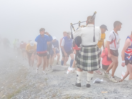 Interlaken / Switzerland - September 09 2008 : Marathon runners passing the highest point in the clouds of the Jungfrau Marathon where the bagpiper is playing between the Eiger north face and the moraine