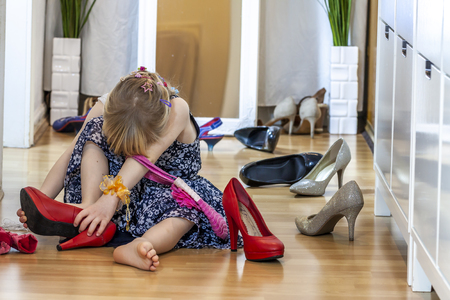 Little girl wearing big high-heeled mothers shoes