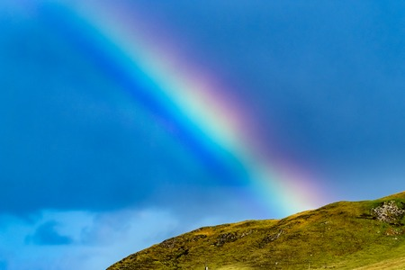 Close up of beautiful natural rainbow above a hill