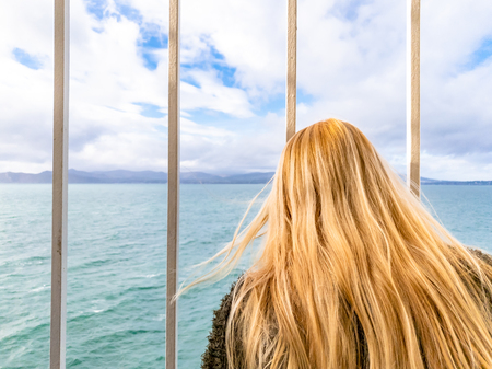Blond Lady looking through the bars and looking to sea and land Stock Photo