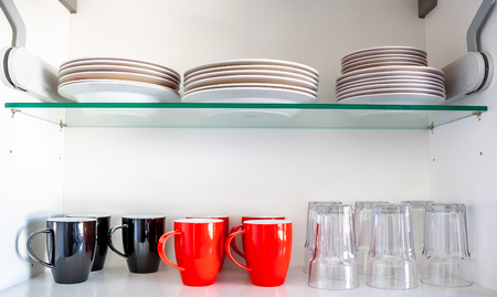 Kitchen cupboard with disheslike plates, cups and glasses Stock Photo