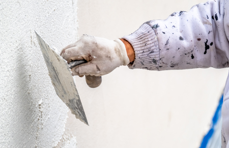Construction worker plastering and smoothing concrete wall with cement