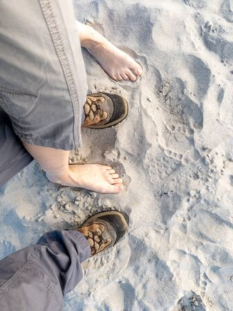 Couple feet and shoes standing on the sandy beach