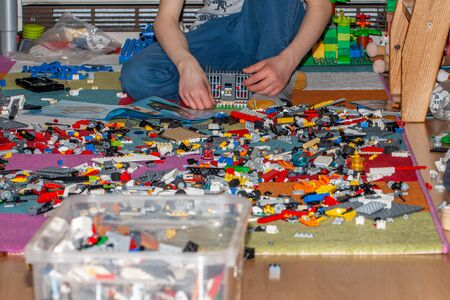 Essen / Germany - March 27 2019: Boy playing with Lego, plastic construction toys that are manufactured by The Lego Group in Billund, Denmark Editorial