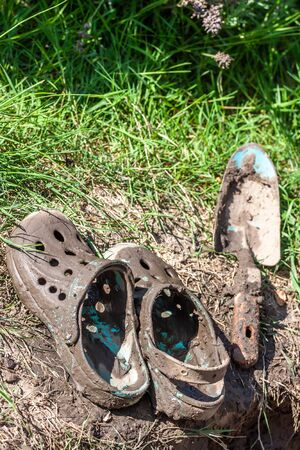 Garden clogs and shovel standing on the mud