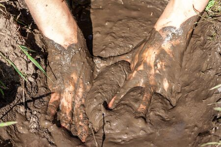 Boy working and playing in the mud.