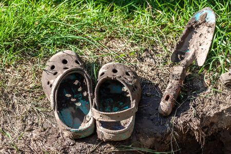 Garden clogs and shovel standing on the mud. Фото со стока