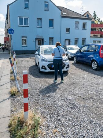 Moers / Germany - August 16 2019 : German parking inspector taking notes to issue a parking fine