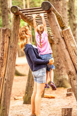 Mother Supporting daughter in the playground with climbing and hanging on a ladder