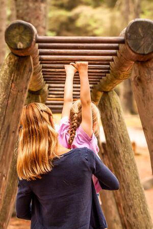Mother Supporting daughter in the playground with climbing and hanging on a ladder Reklamní fotografie - 130685373