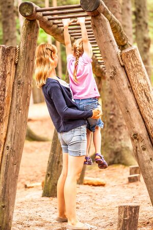 Mother Supporting daughter in the playground with climbing and hanging on a ladder Reklamní fotografie - 130685421