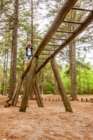 Lady having fun climbing on ladder in the forest