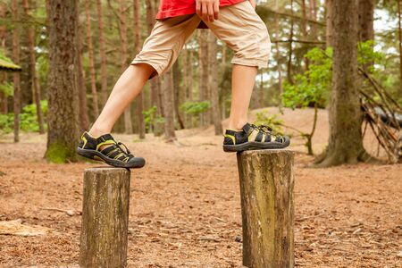 Boy balancing on trees - jumping from one to the other 写真素材