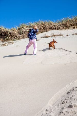Little girl climbing up dune in the summer with dog