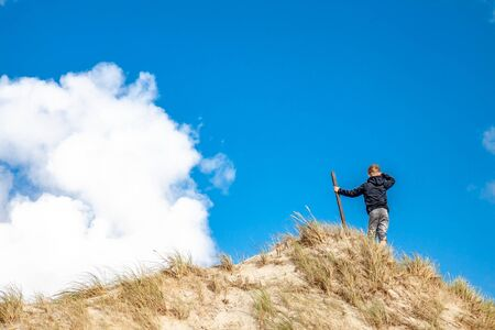Young boy with stick standing on top of sand dune