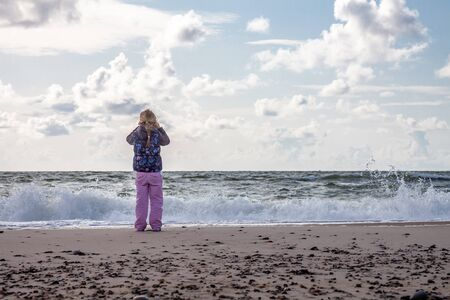 Little girl standing on the beach in the Netherlands Banco de Imagens