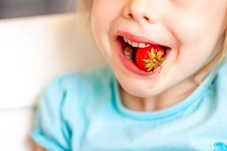 Close up of little girl eating fresh strawberry