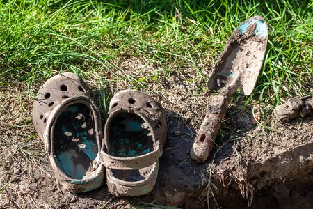 Garden clogs and shovel standing on the mud Archivio Fotografico - 133485321