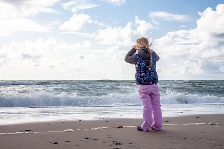 Cute little girl playing on the sandy beach. Happy child wearing warm floral print jacket, pom pom hat and scarf playing outdoors on fall, winter or spring day. Family enjoying winter walk in nature.