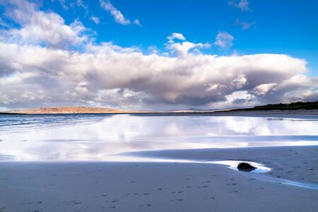 Clouds reflecting on the wet sandy beach Banco de Imagens