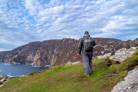 Tourist standing at Slieve League Cliffs which are among the highest sea cliffs in Europe rising 1972 feet above the Atlantic Ocean - County Donegal, Ireland Banco de Imagens