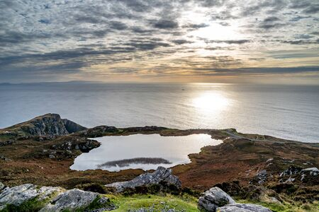 Sunset above the lake at Slieve League Cliffs which are among the highest sea cliffs in Europe rising 1972 feet above the Atlantic Ocean - County Donegal, Ireland