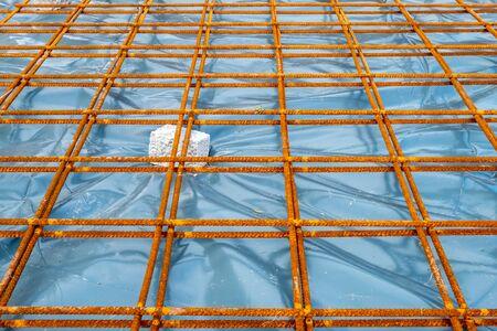 Metal reinforcement grid and wood frame for reinforced concrete basement construction