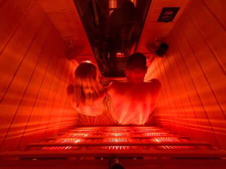 Happy couple relaxing in a luxury infrared sauna.