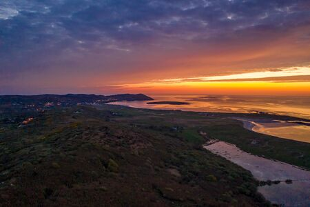 Aerial of sunset above Clooney, Narin and Portnoo in County Donegal - Ireland.