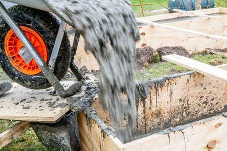 Pouring concrete into wooden frame with wheel barrow