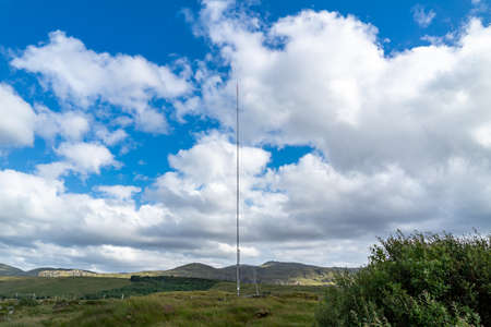 Street view of transmitter tower on an agricultural field in the irish highlands by Glenties in County Donegal.