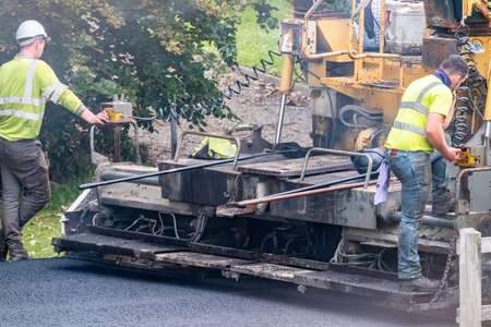 Donegal , Ireland - June 12 2020 : Builder trying to repair Asphalting paver machine during the reopening after Covid 19 lockdown Redakční