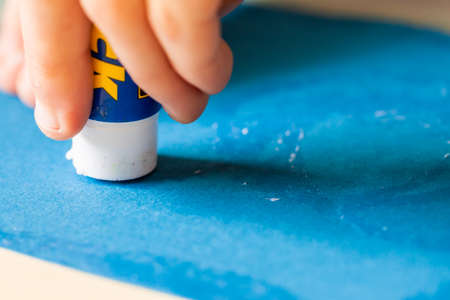 Applying glue stick to the blue paper Stock fotó