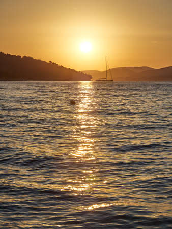 Sunset on the beach in the Croatian town of Okrug Gornji. Sailing ship on the background of mountains