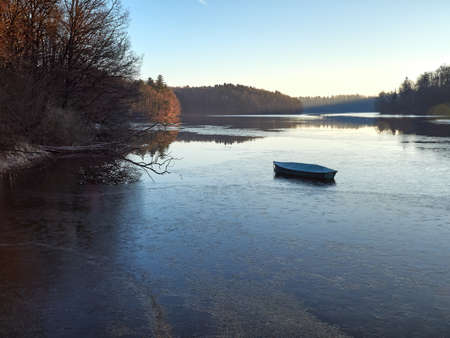 A lonely fishing boat on a partly frozen lake. Water reservoir at the Neyetalsperre dam in the German city of Wipperfurth. Water surface partially frozen. A frosty morning in the Bergisches Land.