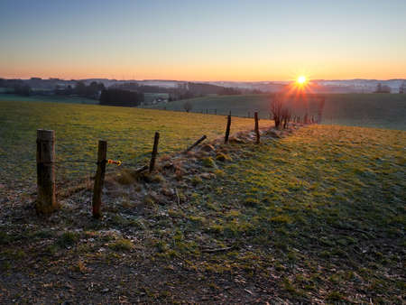 Frosty sunrise in the German city of Wipperfurth. A beautiful countryside landscape in the Bergisches Land region. Green pastures covered with frost in the rays of the rising sun. Imagens