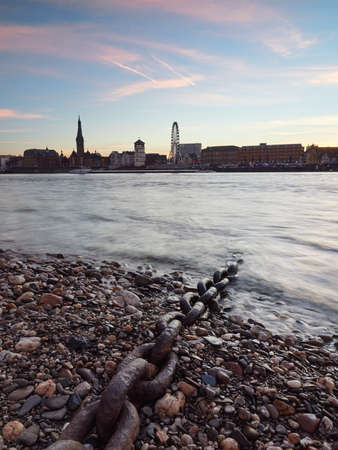 View of the old town with the promenade in the city of Dusseldorf from the bank river Rhine. Beautiful panorama of the city just before sunrise. Imagens