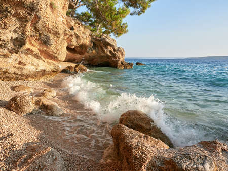 A small, charming pebble beach hidden under a cliff in the Croatian town of Brela. The turquoise waves of the Adriatic Sea crashing against the rocks in a beautiful little bay.