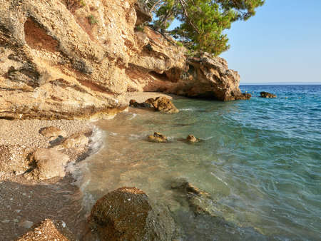 A small, charming pebble beach hidden under a cliff in the Croatian town of Brela. A beautiful cove on the shores of the Adriatic Sea, lit by the rays of the sun.
